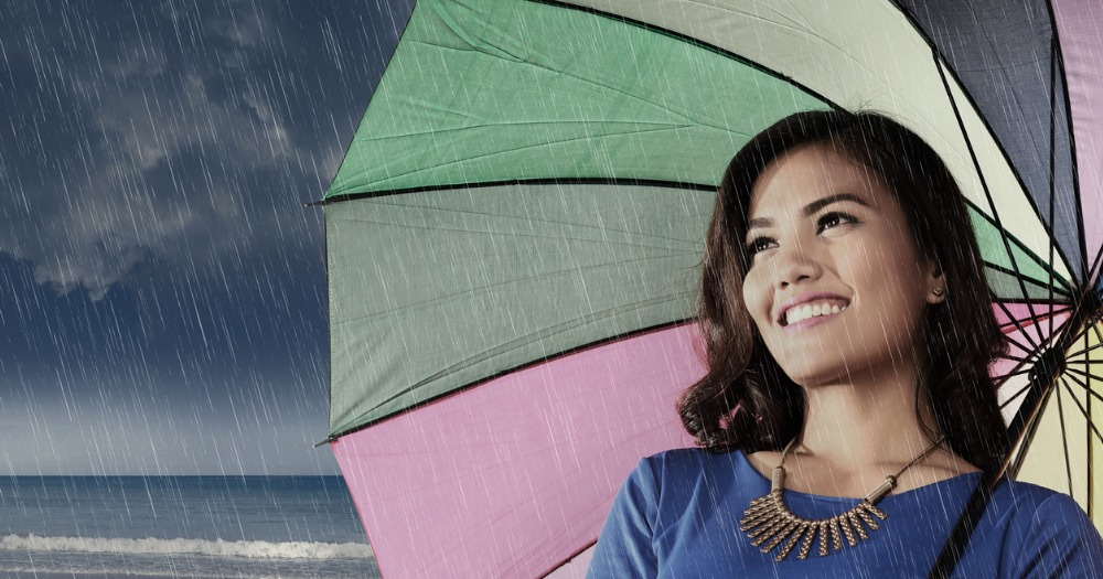 Young Asian woman smiles at the storm on the beach as she is protected under the umbrella she is holding.