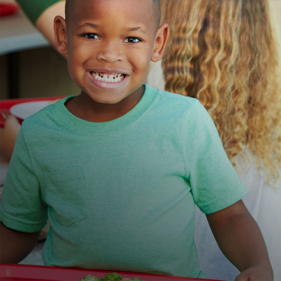 Example photo of smiling elementary student at lunch