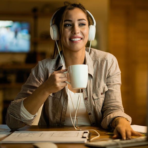 Woman wearing headset and holding a cup of coffee