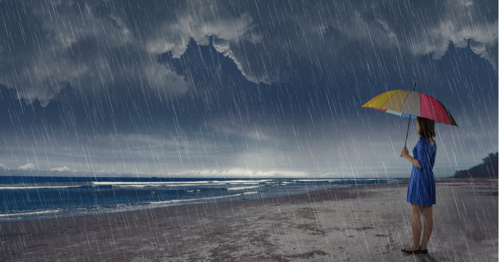 Young Asian woman standing on a beach in the rain holding a multi-colored beach umbrella looking at stormy seas.