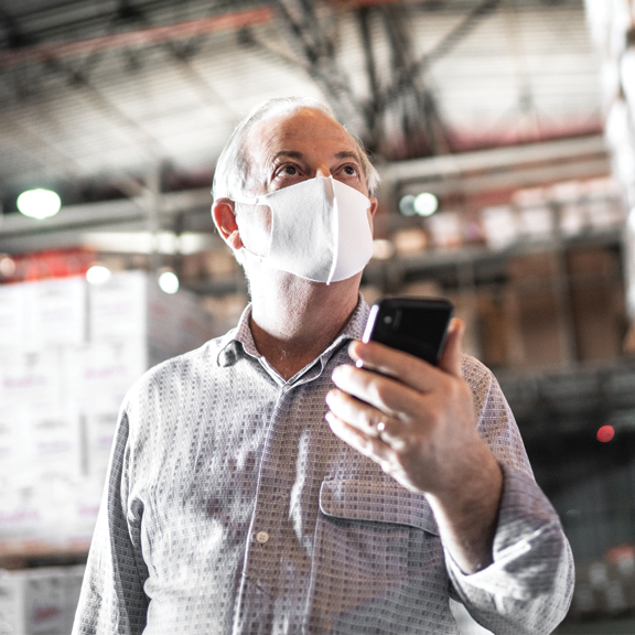 Man wearing a mask looking at mobile device